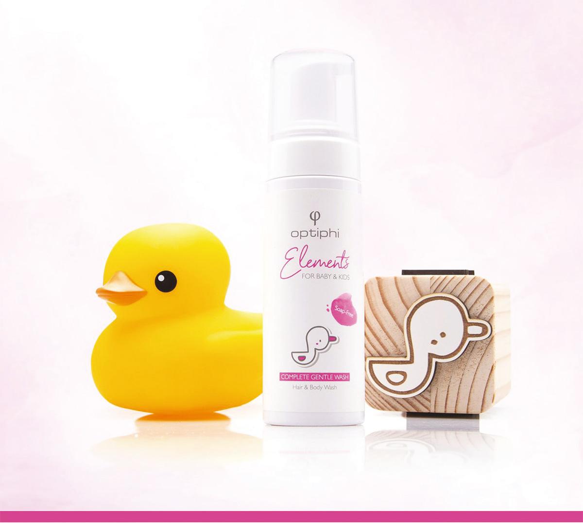 Produktfoto: Weiße Pumpflasche mit Aufschrift in Pink. Baby Haar und Bodywaschgel. Rechts ein Holzwürfel der eine Zeichnung mit einer Ente zeigt. Links eine gelbe Badeente