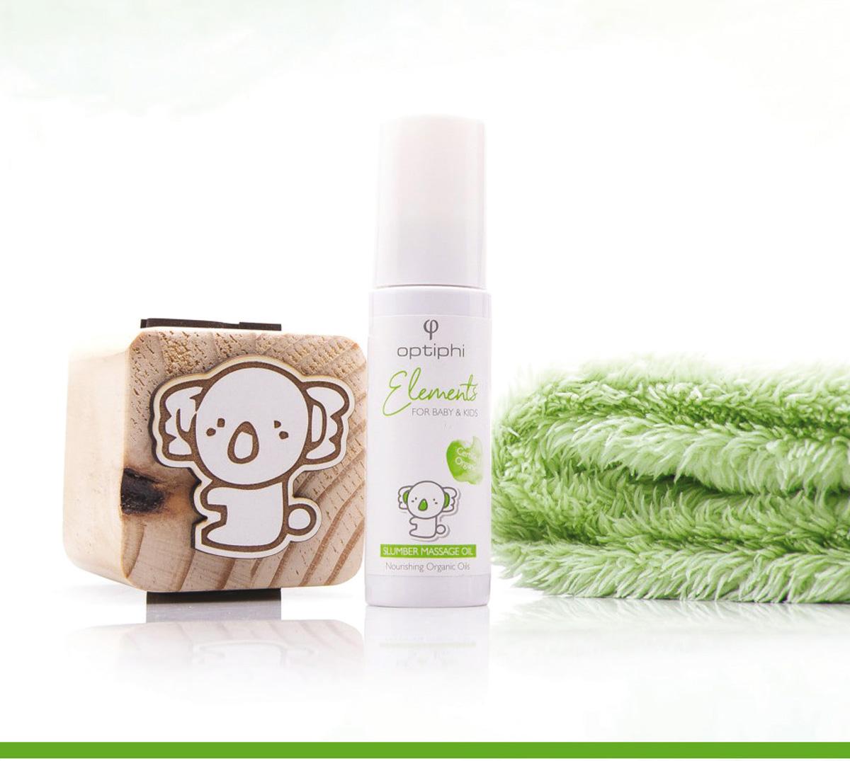 Produktfoto: Weiße Pumpflasche mit grüner Aufschrift Baby Massage Öl rechts ein grünes Kuschelhandtuch, links ein Holzwürfel mit einer Zeichnung die einen Koalabär zeigt