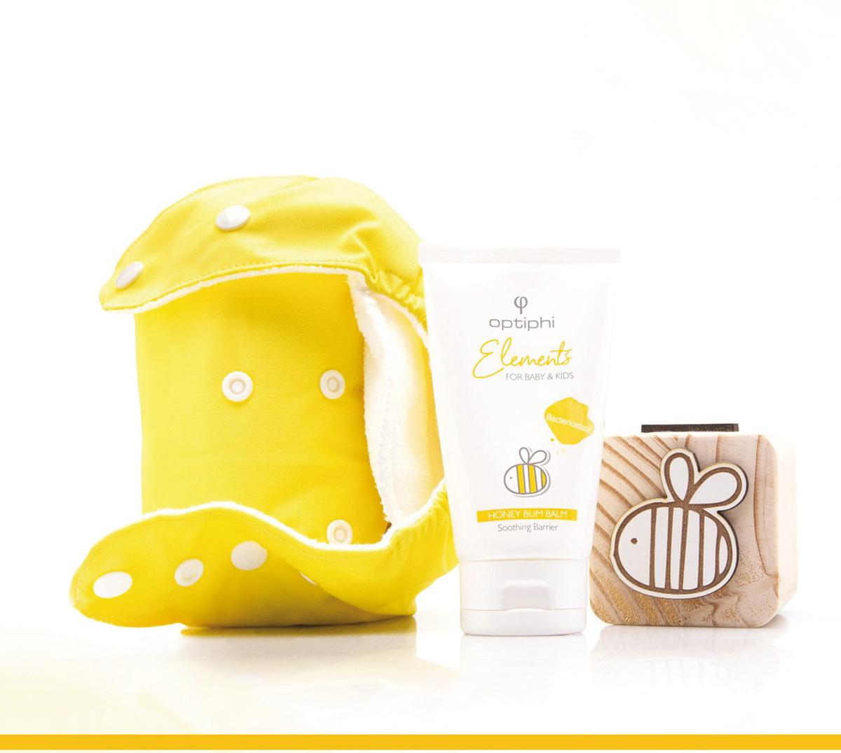 Produktfoto: Gelbe kleine Produkttasche. In der Mitte eine weiße Tube mit gelber Aufschrift Baby Bum, links Holzwürfel mit Skizze einer Biene.