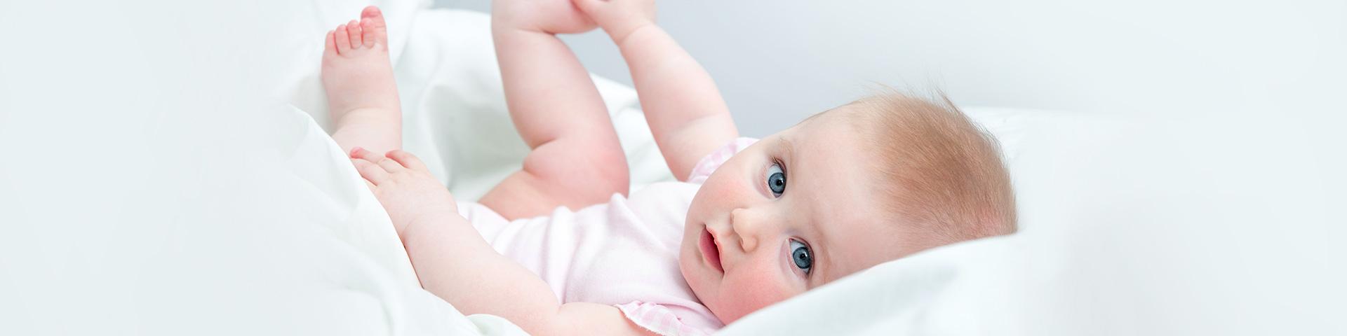 Babykosmetik Baby liegt in weichen Polstern und schaut mit blauen Augen neugierig in die Kamera