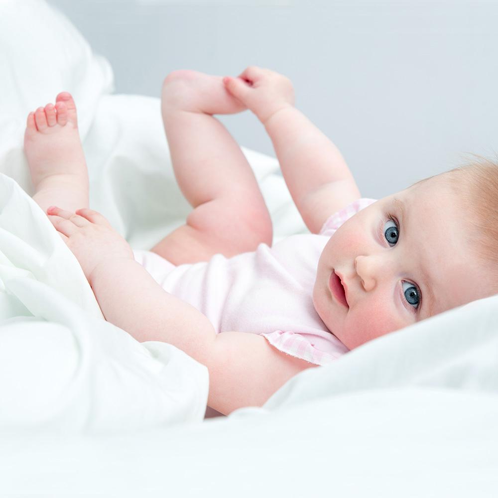 Babypflege Baby mit blauen Augen hält ihr nacktes Füßchen