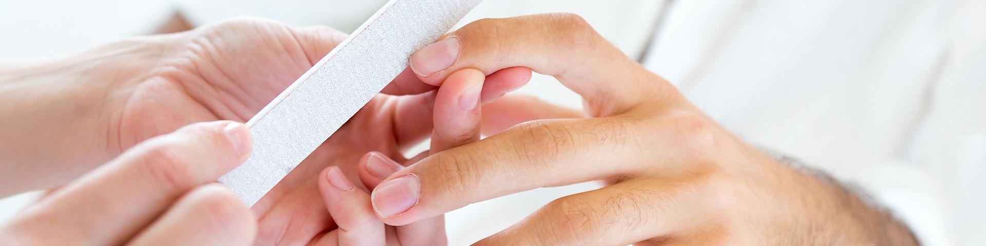 Maniküre für Männer. Eine Frauenhand feilt die Fingernägel einer Männerhand