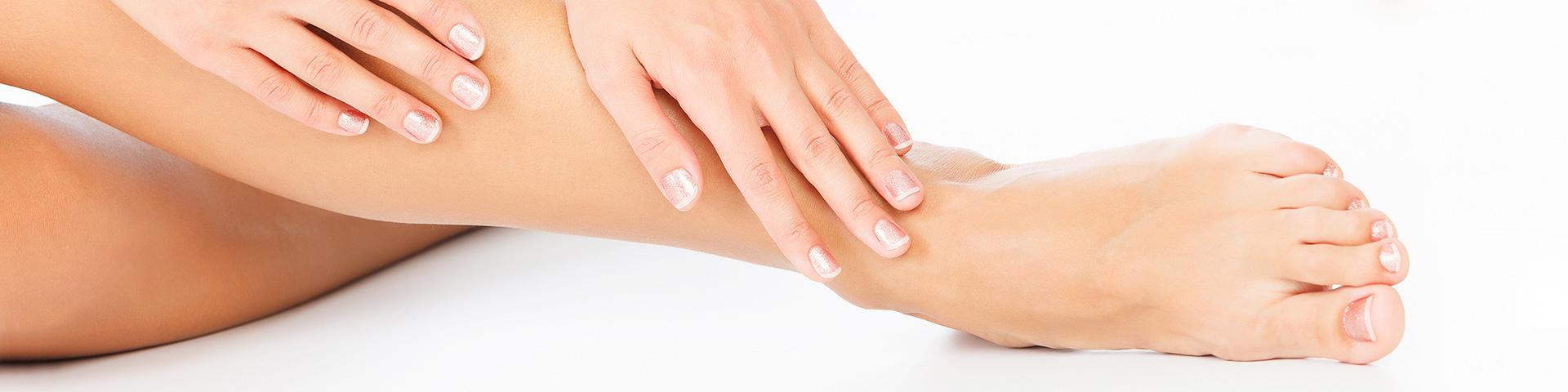 Schön manikürte Hände greifen zu schön lackierten Füßen