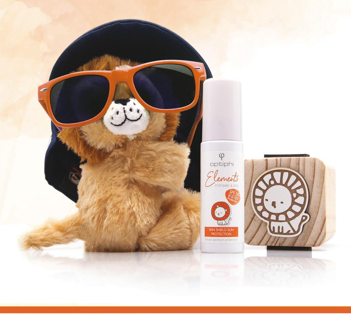 Babykosmeitk Kleiner Plüschlöwe mit rotbrauner viel zu großer Sonnenbrille und zu großen schwarzen Hut mit Baby Sonnenpflege Produkt und Holzwürfel mit handgemalten Löwen