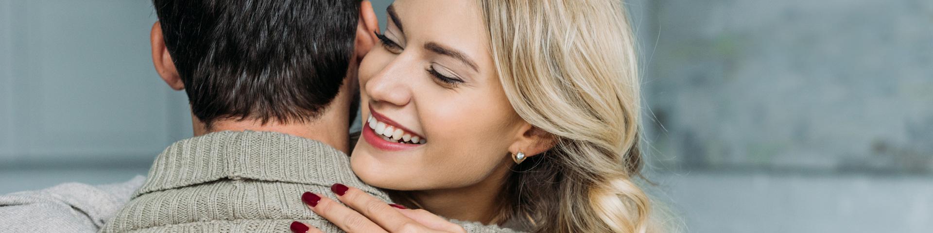 Lächelnde junge Frau umarmt einen Mann. Ihn sieht man nur von hinten