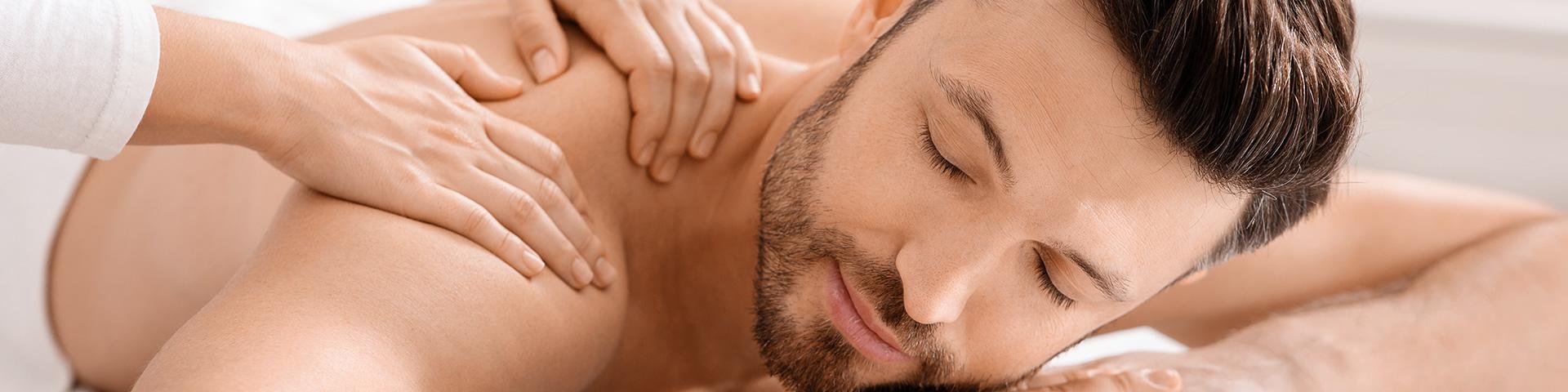 Massage für Männer Junger Mann mit Bart liegt entspannt am Bauch. Er wird an der Schulter massiert