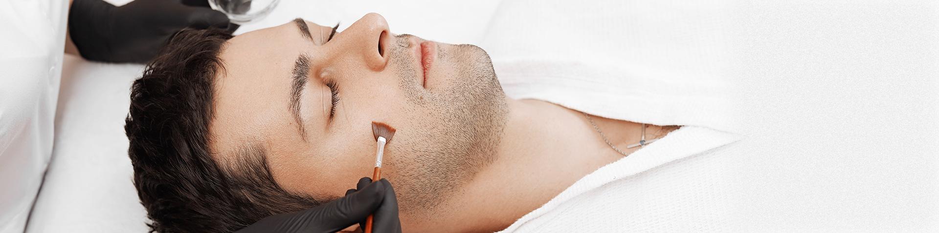 Peeling für Männer. Entspanntes Männergesicht in der Kosmetikbehandlung. Mit einem Pinsel wird ein Produkt aufgetragen
