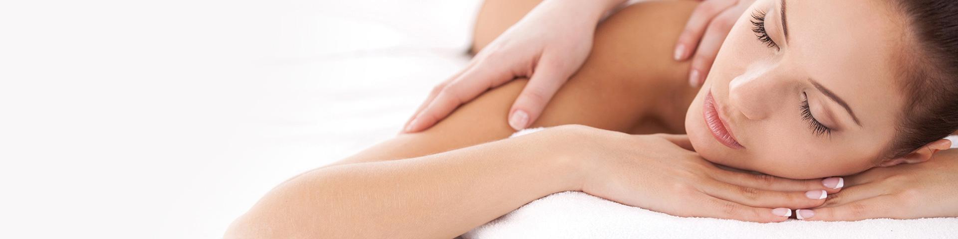 Junge Frau liegt auf ihren schön manikürten Händen und wird an der Schulter massiert