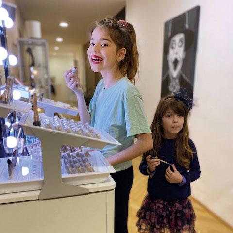 2 Mädchen vorm Schminktisch die größere versucht einen knallroten Lippenstift, die Kleinere hält einen Pinsel