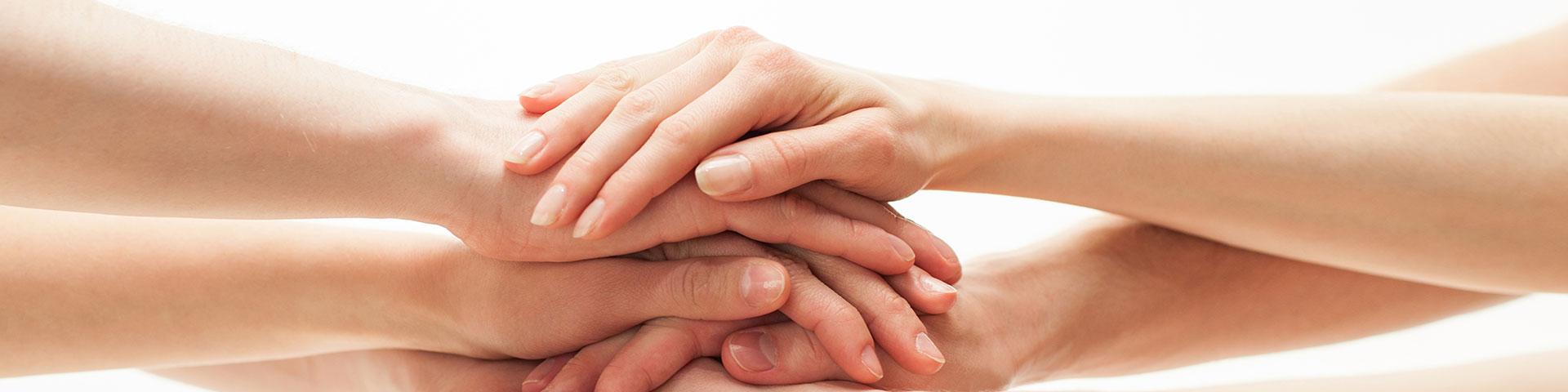 Symbolfoto verschiedene Hände liegen übereinander